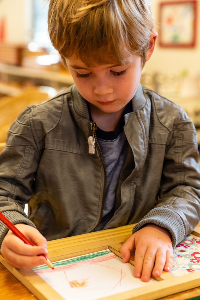 Montessori boy drawing independently
