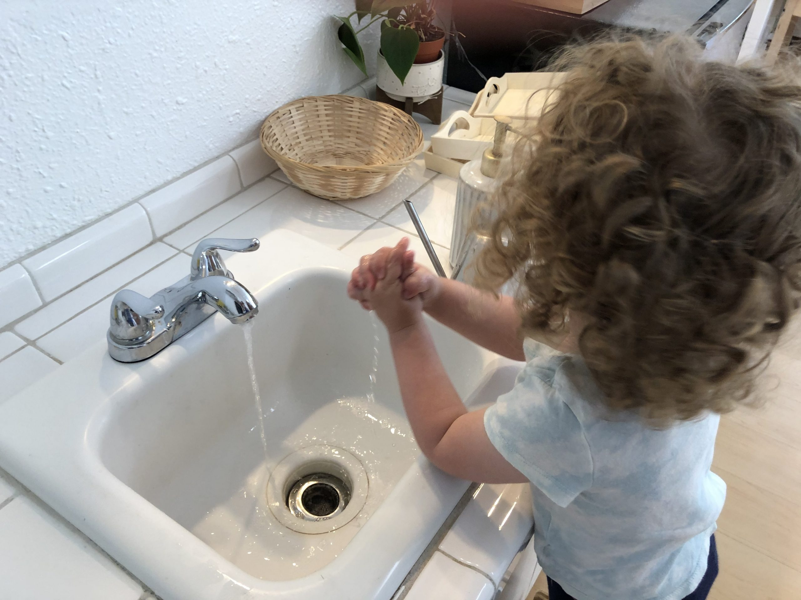 Toddlers learn how to wash their hands with a child size sink